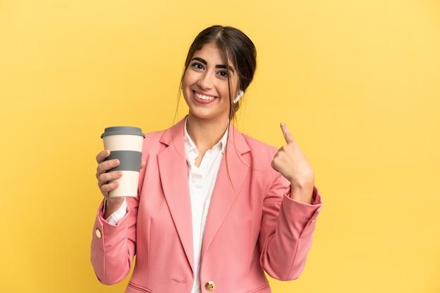 Biznesowa kaukaska kobieta odizolowana na żółtym tle dająca gest kciuka w górę