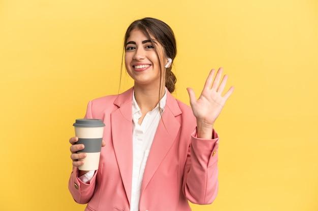 Biznesowa kaukaska kobieta odizolowana na żółtym tle pozdrawiając ręką ze szczęśliwym wyrazem twarzy