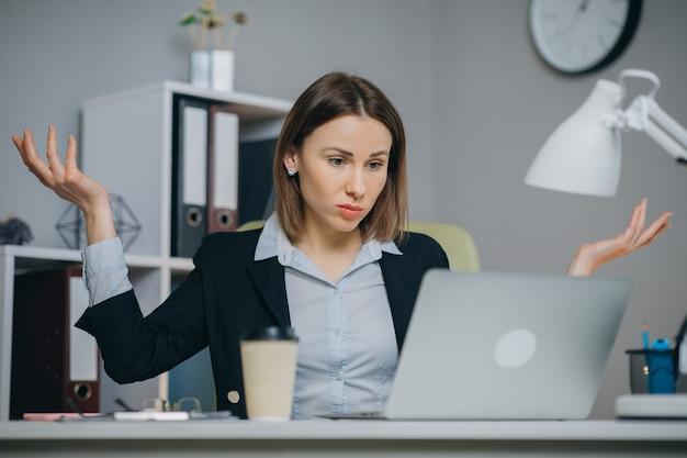Biznesowa kobieta czyta złą wiadomość na laptopie przy coworking przestrzenią. wzburzona kobieta zamyka puszek laptop w biurze. zmęczona kobieta oddycha głęboko w miejscu pracy.