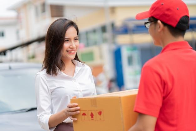 Biznesowa kobieta dostaje pudełko od dostawy do domu