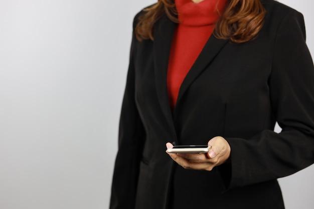 Biznesowa kobieta jest ubranym czarnego i czerwonego garnituru munduru mienia i patrzeje telefon komórkowego z ufnym