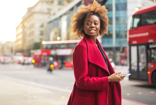 Biznesowa kobieta jest ubranym czerwonego żakiet, chodzi na ulicie