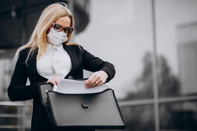 Biznesowa kobieta jest ubranym maskę na zewnątrz centrum biznesu