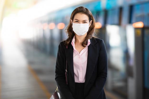 Biznesowa kobieta jest ubranym maskowego czekanie dla pociągu.