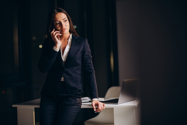 Biznesowa kobieta korzystająca z telefonu w biurze i pozostająca do późna w nocy