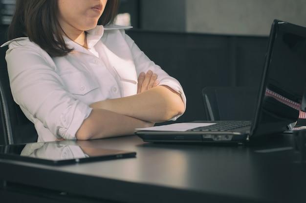 Biznesowa kobieta krzyżował ręki na biurku