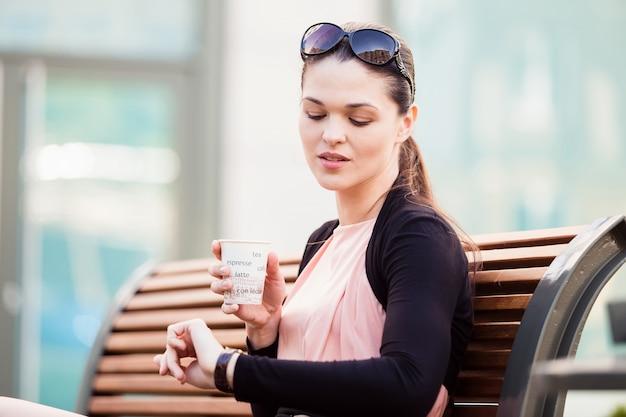 Biznesowa kobieta na kawowej przerwie, patrzeje zegar na ręce