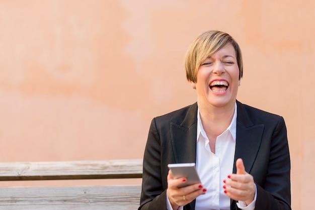 Biznesowa kobieta ono uśmiecha się z telefonem komórkowym na ręce
