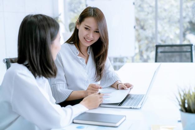 Biznesowa kobieta opowiada i dzieli wycieczka pic z ostatniego weekendu z jej przyjacielem w biurze
