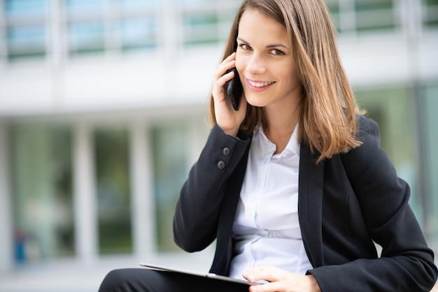 Biznesowa kobieta opowiada na jej mobilnym telefonie komórkowym