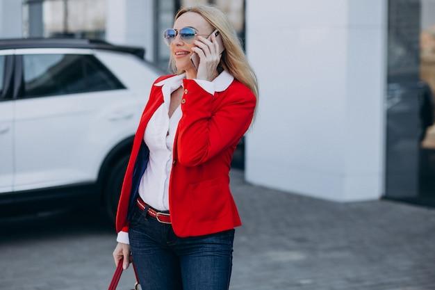 Biznesowa kobieta opowiada na telefonie na zewnątrz biurowego centrum