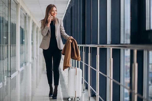 Biznesowa kobieta opowiada na telefonie w terminal z podróży torbą