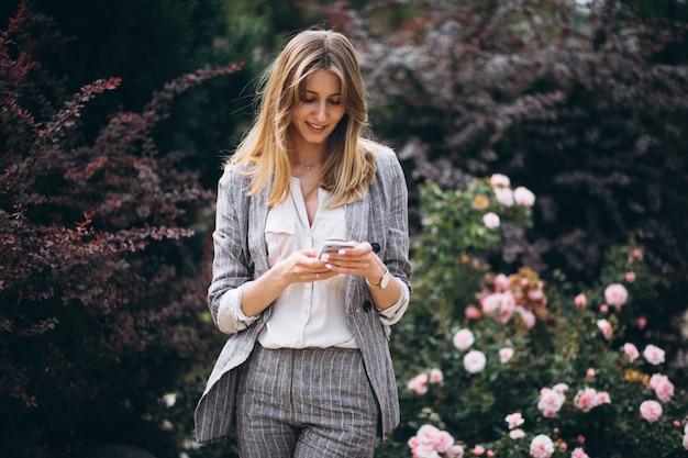 Biznesowa kobieta opowiada na telefonie w ulicie w kostiumu