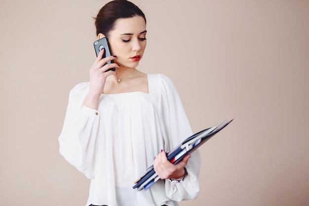 Biznesowa kobieta opowiada na telefonie z dokumentami w jej rękach