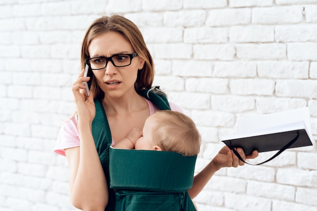 Biznesowa kobieta opowiada telefon i trzyma nowonarodzonego.