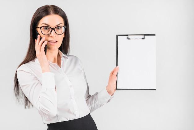 Biznesowa kobieta opowiada telefonem pokazuje schowek