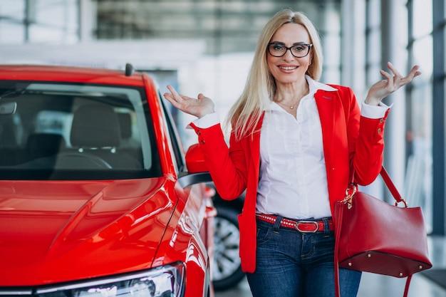 Biznesowa kobieta patrzeje dla samochodowej wiszącej ozdoby przy samochodową sala wystawową