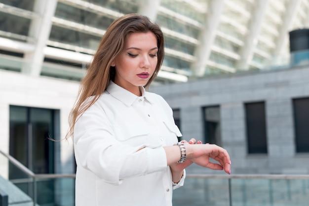 Biznesowa kobieta patrzeje jej zegarek