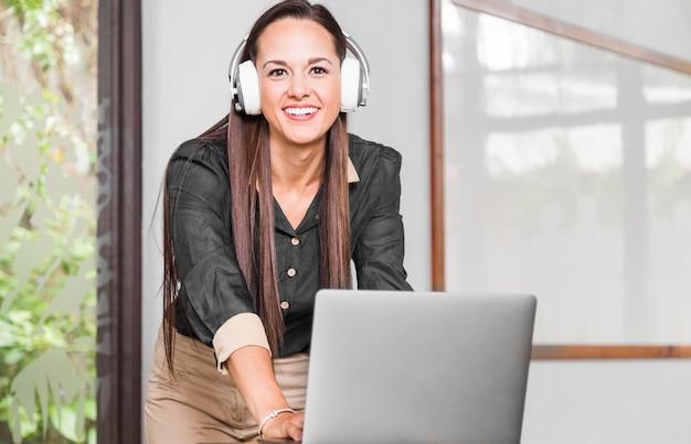 Biznesowa kobieta patrzeje kamerę z hełmofonami