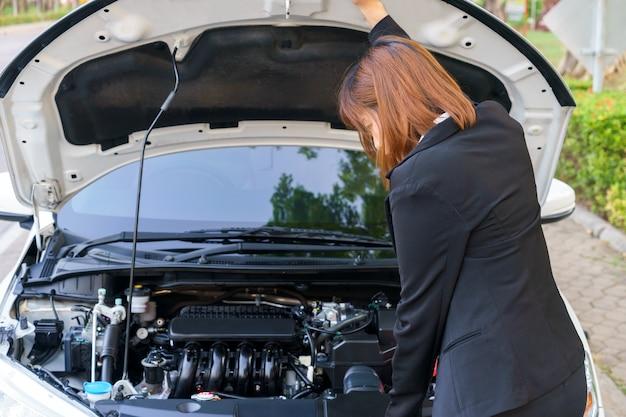 Biznesowa kobieta patrzeje silnika z samochodową awarią