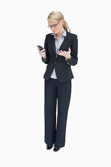 Biznesowa kobieta patrzeje ze złością przy telefonem komórkowym