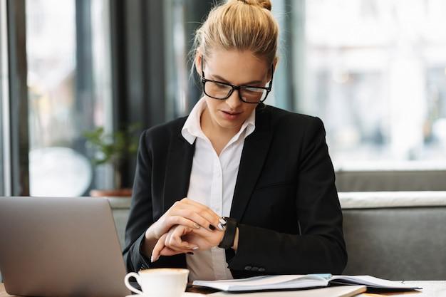 Biznesowa kobieta patrzeje zegarek.