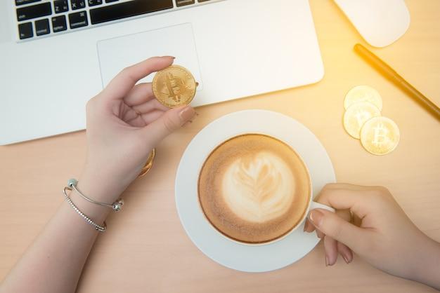 Biznesowa kobieta pije kawę, herbaty i używa laptop w biurze, bitcoin w ręce