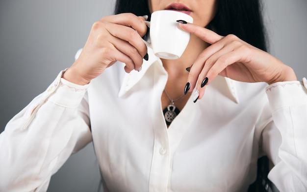 Biznesowa kobieta pije kawę w biurze.