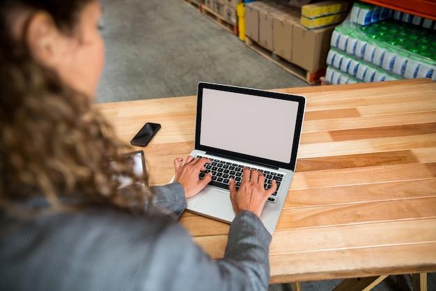 Biznesowa kobieta pisać na maszynie na jej laptopie