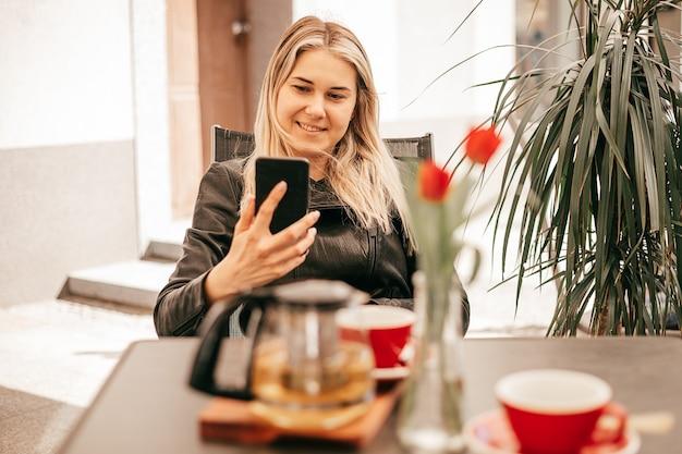 Biznesowa kobieta podczas przerwy na kawę w kawiarni komunikuje się na smartfonie lub robi selfie