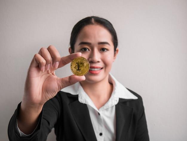 Biznesowa kobieta pokazuje złocistego bitcoin.