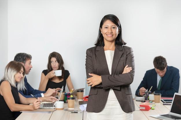Biznesowa kobieta pozuje w kostiumu przy biurem