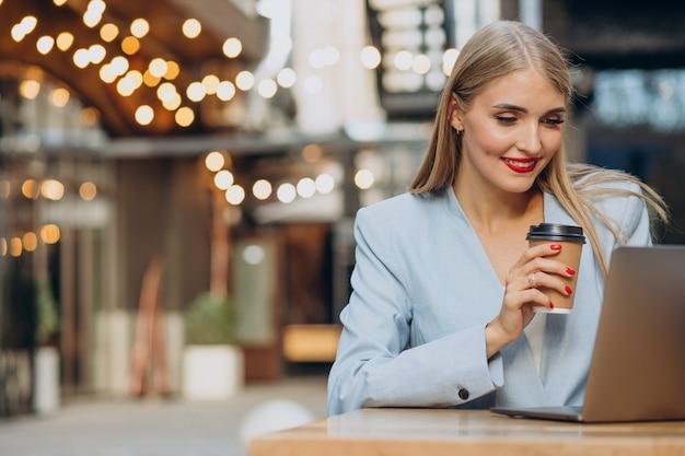 Biznesowa kobieta pracuje na komputerze w kawiarni i pije kawę