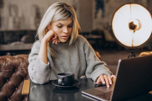 Biznesowa kobieta pracuje na komputerze w kawiarni