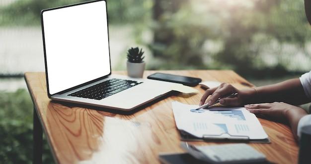 Biznesowa kobieta pracuje na laptopie z wykresem biznesowym