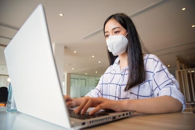 Biznesowa kobieta pracuje od domu będący ubranym maskę ochronną i używa laptop. koronawirus wybuch