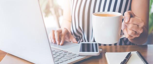 Biznesowa kobieta pracuje przy laptopem i jej ręką trzyma filiżankę kawy.