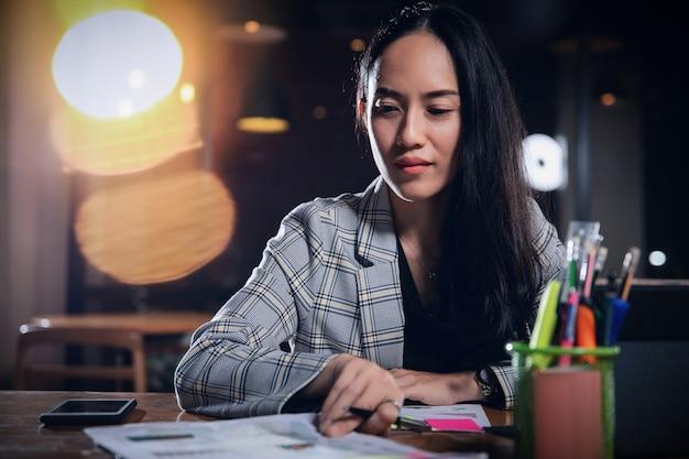 Biznesowa kobieta pracuje samotnie w biurze przy nocą.