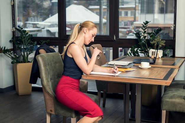 Biznesowa kobieta pracuje z dokumentami przy biurem.
