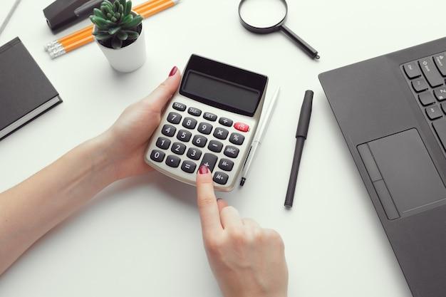 Biznesowa kobieta pracuje z pieniężną dane ręką używać kalkulatora