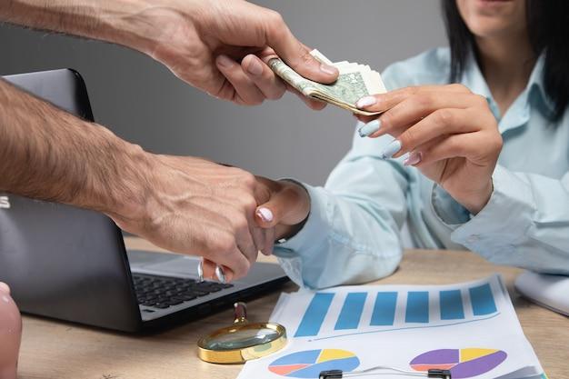 Biznesowa kobieta przy stole bierze łapówkę