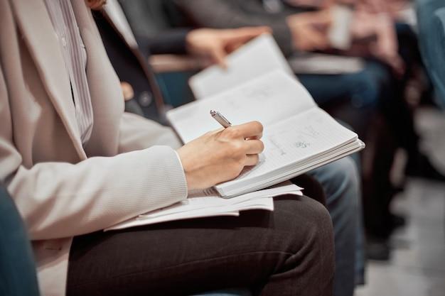 Biznesowa kobieta robi notatki w swoim notatniku