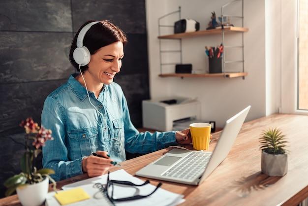 Biznesowa kobieta robi rozmowie wideo przy biurem