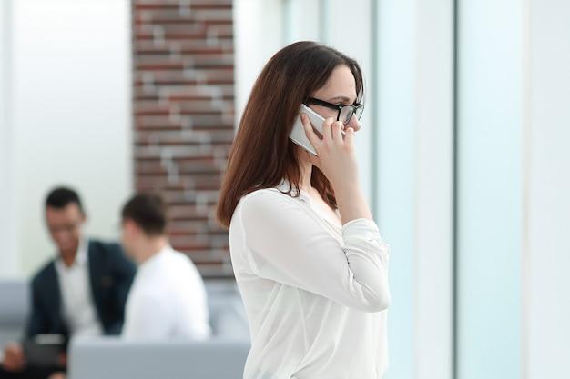 Biznesowa kobieta rozmawia na smartfonie stojąc w biurze