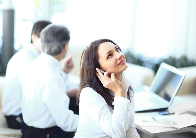 Biznesowa kobieta rozmawia przez telefon komórkowy w biurze