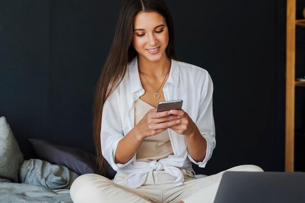 Biznesowa kobieta rozmawia przez telefon, negocjuje, umawia się z przyjaciółmi. uśmiechnięta dziewczyna w białej koszuli siedzi na łóżku, obok laptopa. brunetka dziewczyna na ciemnej ścianie ściany w sypialni.