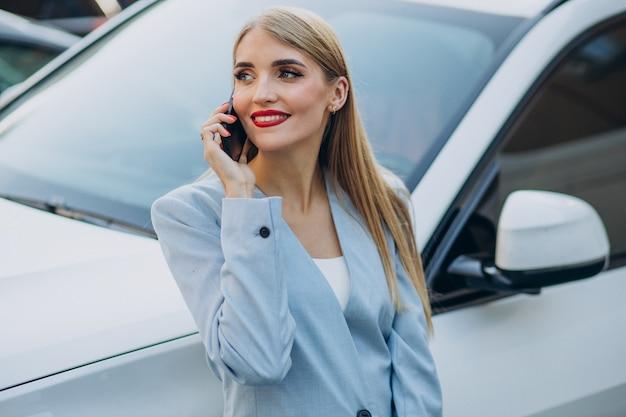 Biznesowa kobieta rozmawia przez telefon przy swoim samochodzie