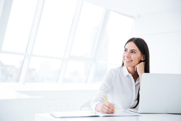 Biznesowa kobieta siedzi przy stole z laptopem i odwraca wzrok w biurze