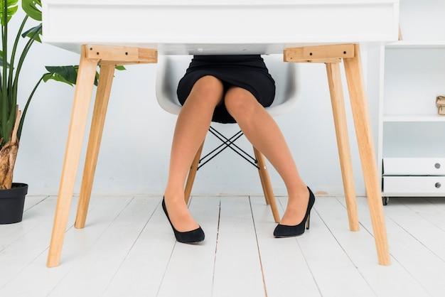 Biznesowa kobieta siedzi przy stołem w spódnicie i butach