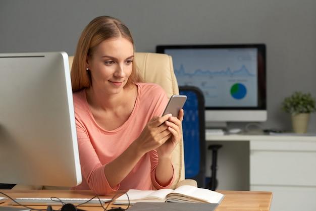 Biznesowa kobieta smsuje prywatne wiadomości przy jej miejscem pracy